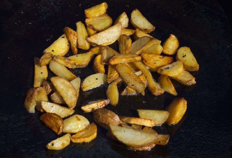 Frieten die in hete olie in een grote pan braden stock afbeelding