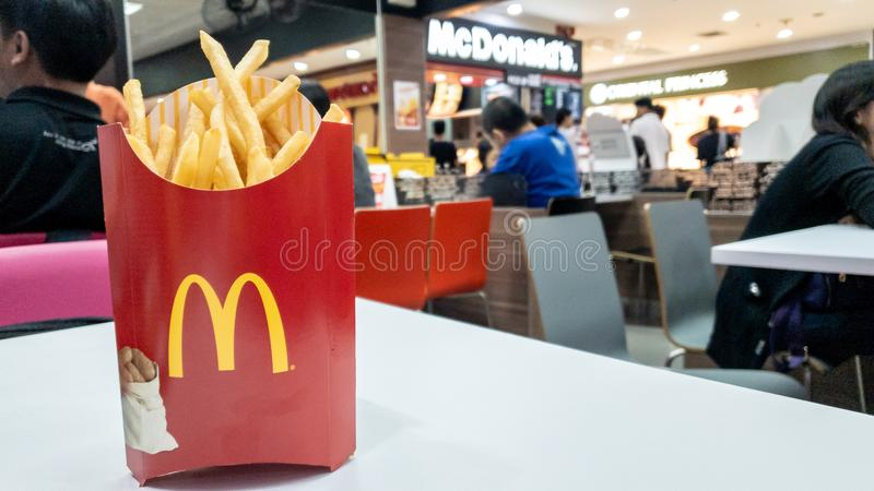 Frietencontainer in rood pakket op witte lijst bij de koffie van McDonald ` s stock foto's