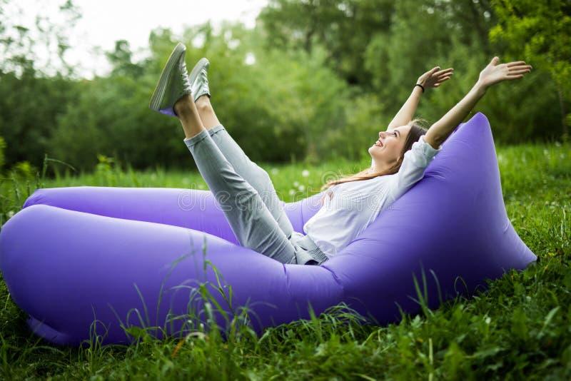 frigör I Den nätta unga kvinnan som ligger på uppblåsbar soffalamzac med reised händer i luften, medan vila på gräs, parkerar in royaltyfri foto