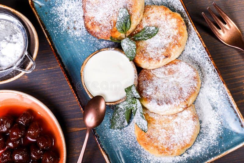Friggendo lo syrniki casalingo dei pancake della ricotta con lo zucchero in polvere, la panna acida, bacche si inceppa sulla fine fotografie stock libere da diritti