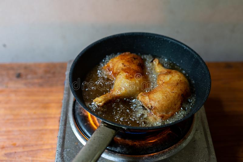 Friggere il pollo in una pentola con olio bollente fotografia stock