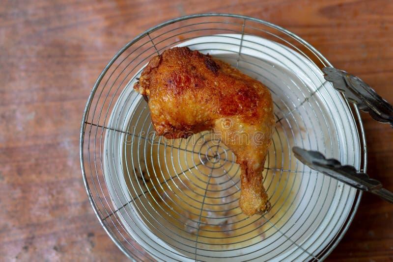 Friggere il pollo in una pentola con olio bollente immagini stock