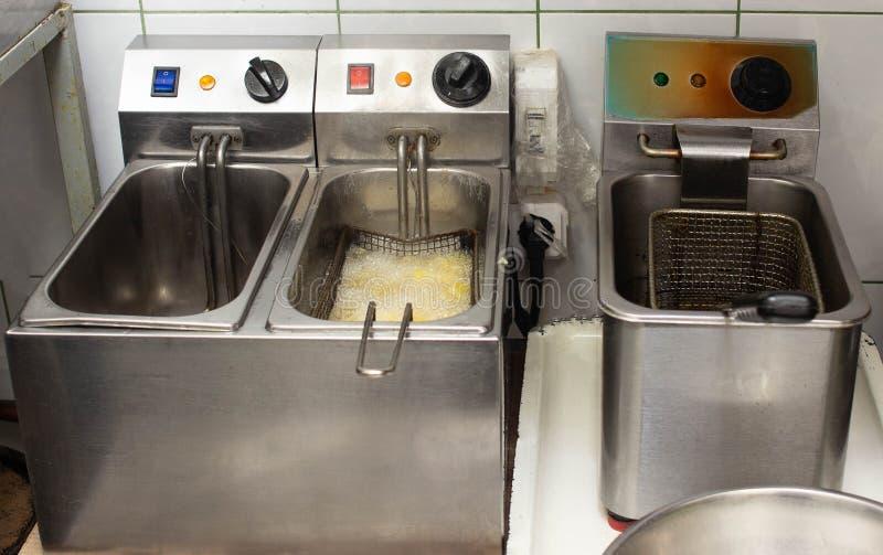 Friggitrici per le patate di torrefazione in petrolio e patate fritte nella cucina nel ristorante immagini stock libere da diritti