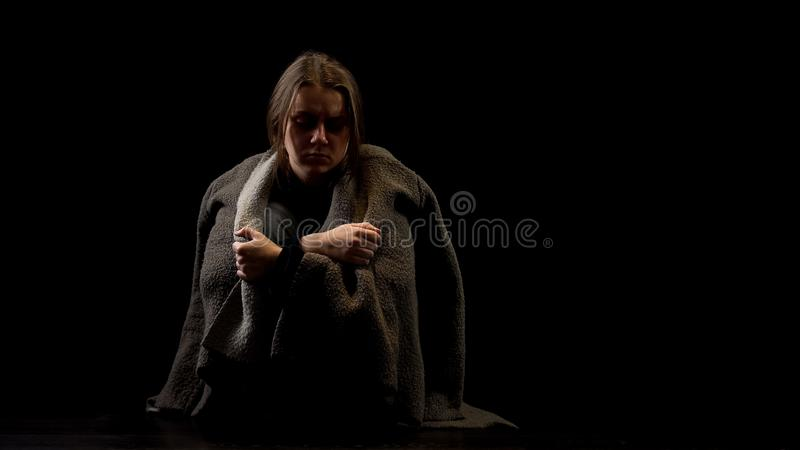 Frightened abused female sitting in darkness, victim of domestic violence. Stock photo royalty free stock images