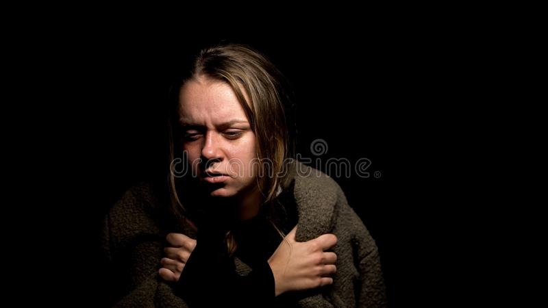Frightened abused woman covering with blanket in darkness, victim of violence royalty free stock photography