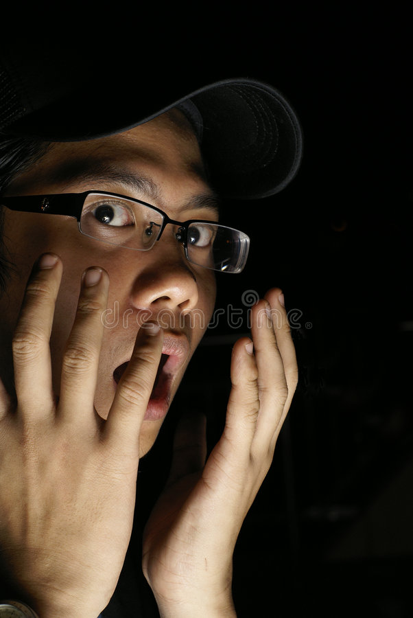 Frightened asian male. Portrait with hands to face with black background stock images