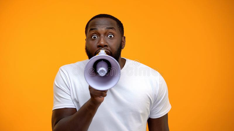Frightened black man screaming in megaphone, spreading information, awareness. Stock photo royalty free stock photo