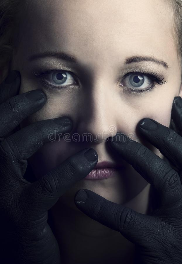 Frightened blonde woman grabbed by black hands on her face artistic conversion royalty free stock image
