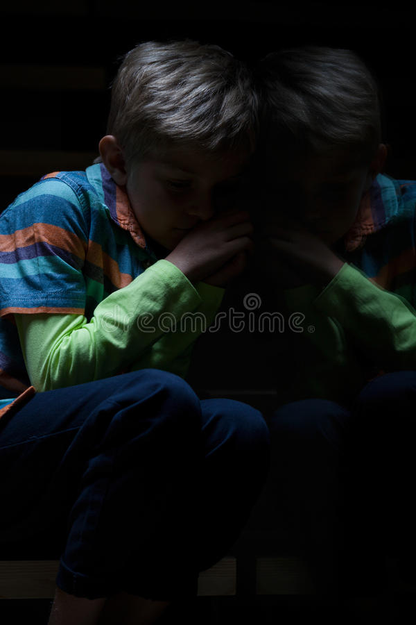 Frightened boy sitting on stairs stock images