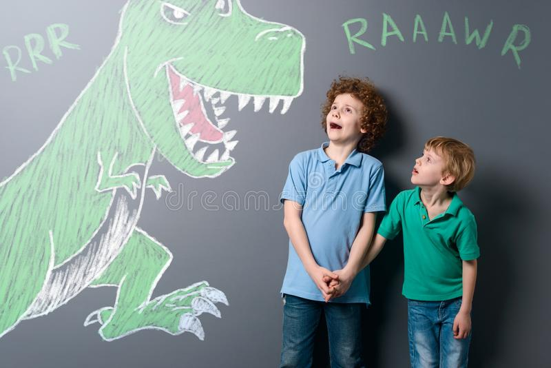Frightened boys and enormous dinosaur. Brothers screaming and looking on jaws of the growling reptile, depicted with chalk on neutral background stock photography