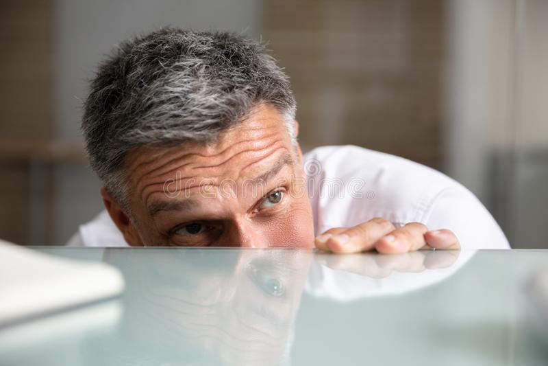 Frightened Businessman Peeking From The Edge Of Desk. Close-up Of A Frightened Businessman Peeking From The Edge Of Reflective Desk stock image