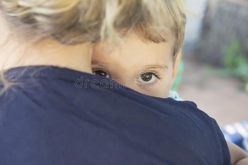 A frightened child hides behind his mother stock photos
