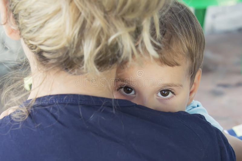 A frightened child hides behind his mother royalty free stock image