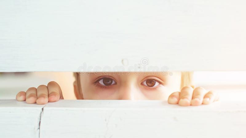 Frightened child is spying through a wooden fence. Scared child boy. Human emotion, facial expression. Sad kid outdoors. Bored lit royalty free stock image