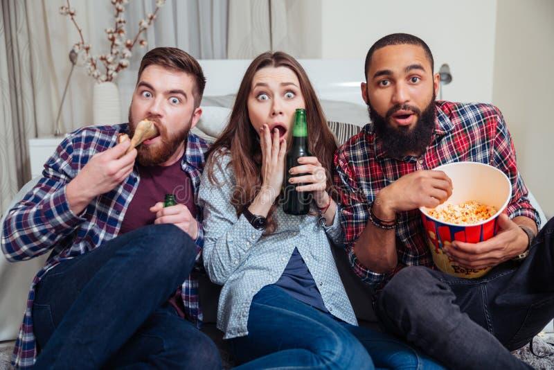 Frightened a choqué la bière potable de personnes et la TV de observation images stock