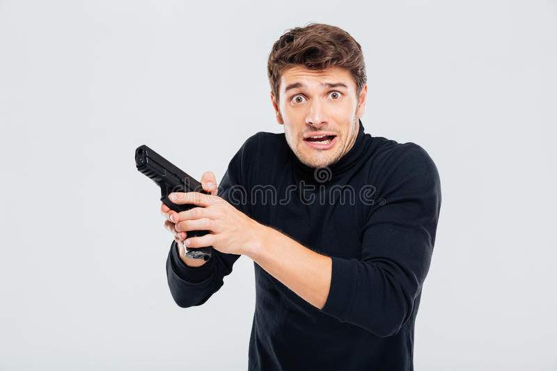 Frightened confused yougn man holding a gun stock photos