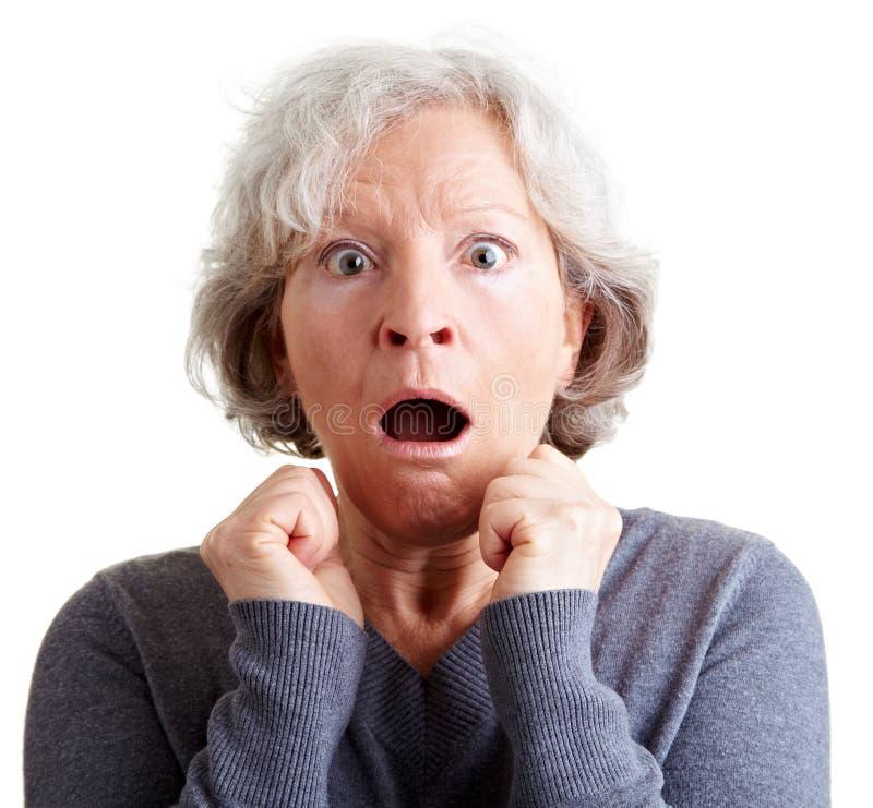 Frightened elderly woman shocked stock photo