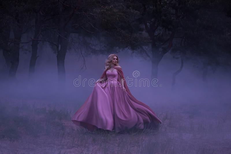 A frightened girl blonde runs away from a forest that has covered a thick fog. On the elf, a luxurious pink dress with a royalty free stock image