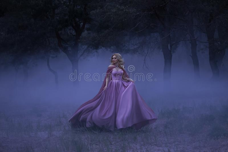 A frightened girl blonde runs away from a forest that has covered a thick fog. On the elf, a luxurious purple dress with stock photos