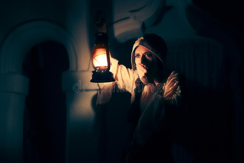 Scared Medieval Woman with Vintage Lantern Outside at Night stock images