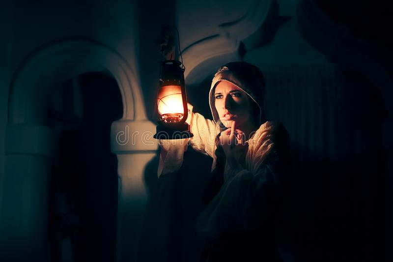 Scared Medieval Woman with Vintage Lantern Outside at Night stock photography