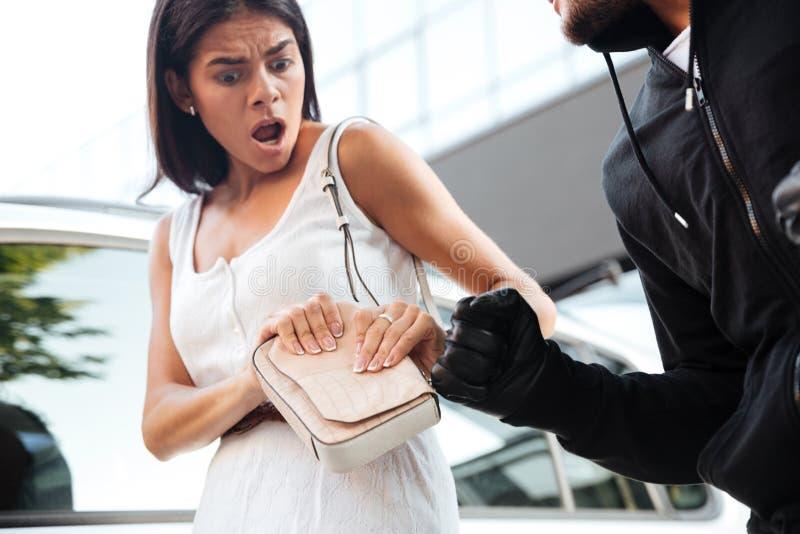 Frightened ha colpito la giovane donna che è vestita dal ladro all'aperto fotografia stock