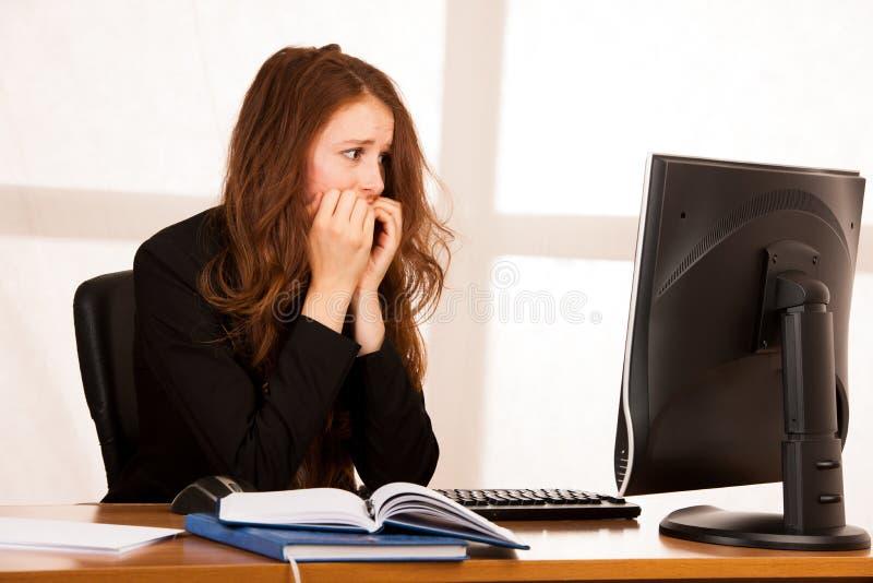 Frightened ha sollecitato la donna che lavora al suo scrittorio nell'ufficio, rea immagine stock libera da diritti