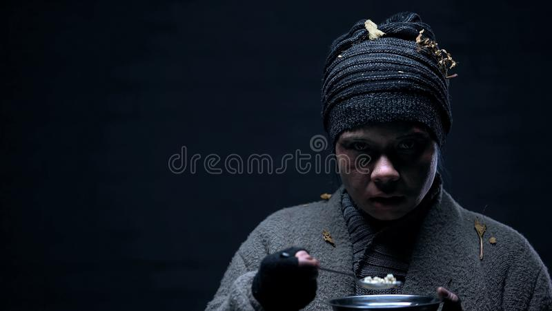 Frightened homeless with bruised face eating ort on black background, violence. Stock photo royalty free stock photo