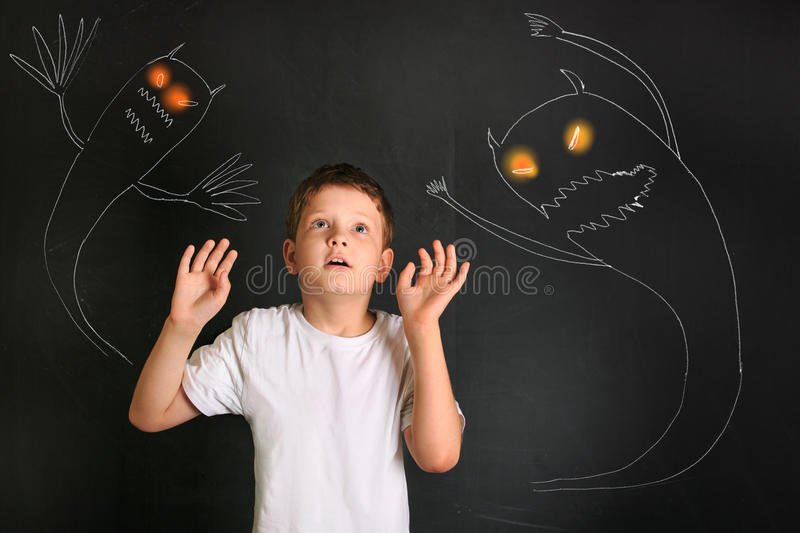 Frightened little boy afraid of night monsters. royalty free stock photography