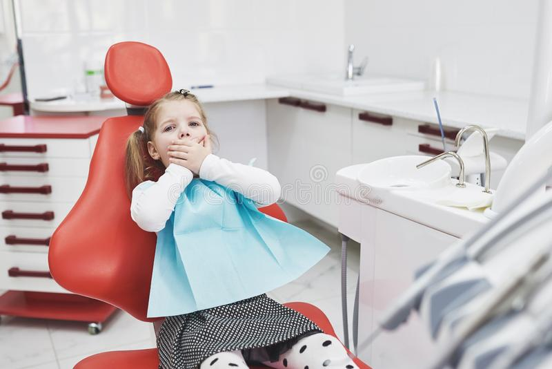 Frightened little girl at dentist office covered mouth with hands stock photo