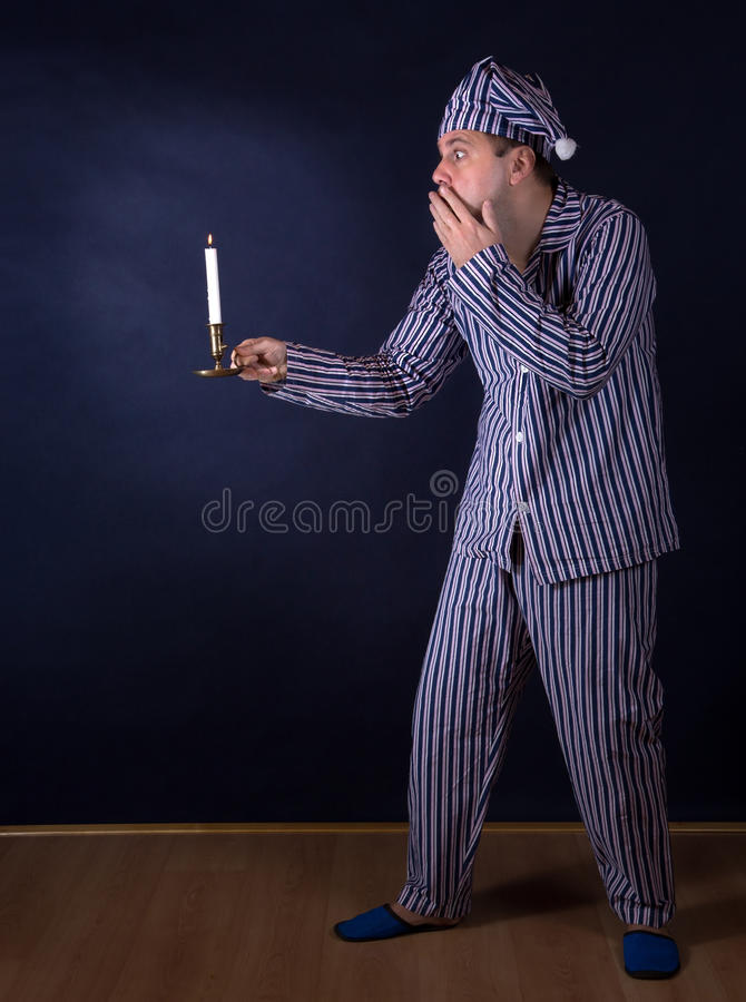 Frightened man in pajamas. Frightened man with candle in pajamas stock photography