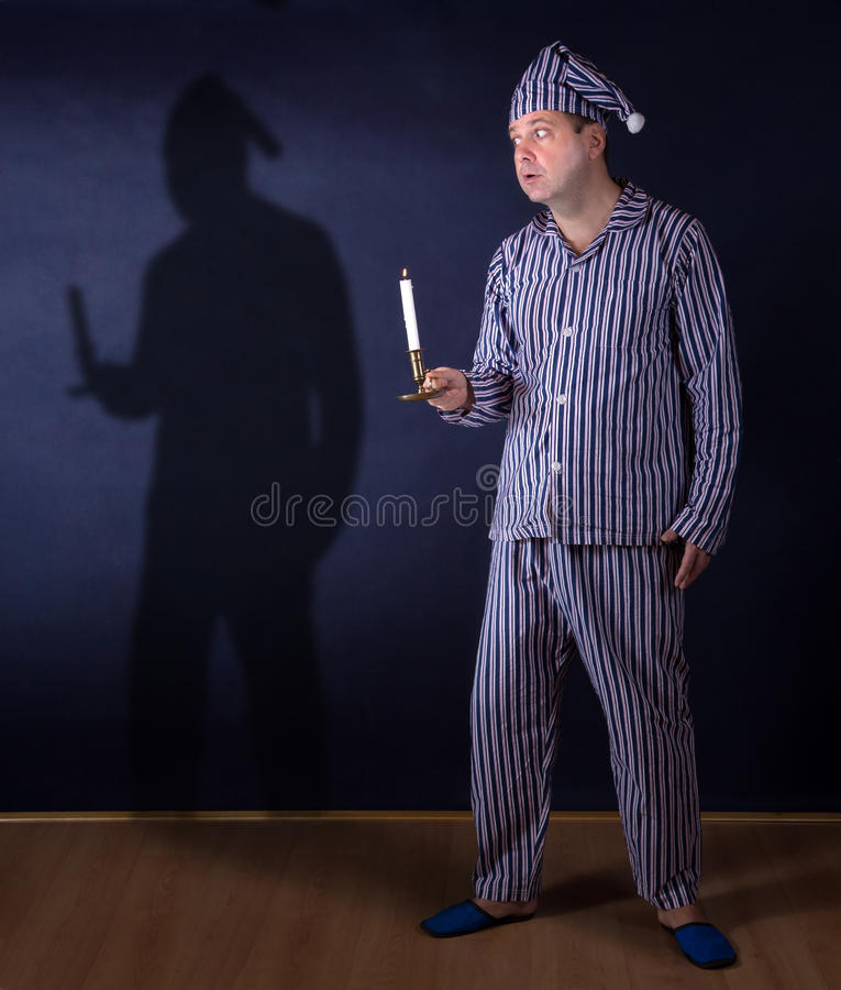 Frightened man in pajamas holding candle. Frightened man with candle in pajamas afraid of his shadow royalty free stock photography