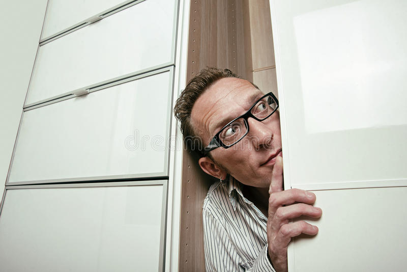 Frightened man peep out white wardrobe. Copy space right royalty free stock image