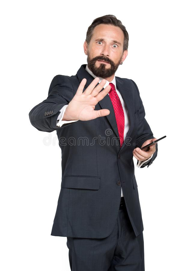 Frightened mature businessman keeping his hand in front of you. Waist up of fearful bearded businessman holding mobile phone while keeping his hand in front of royalty free stock photo