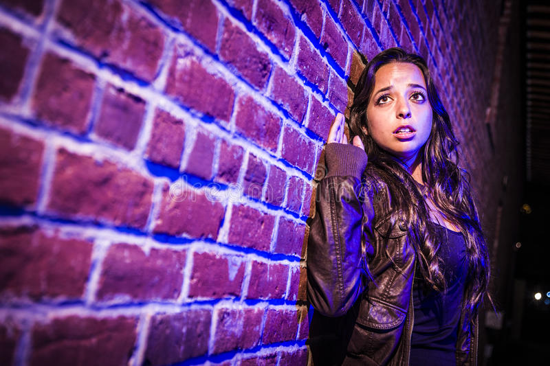Frightened Pretty Young Woman Against Brick Wall at Night stock photos