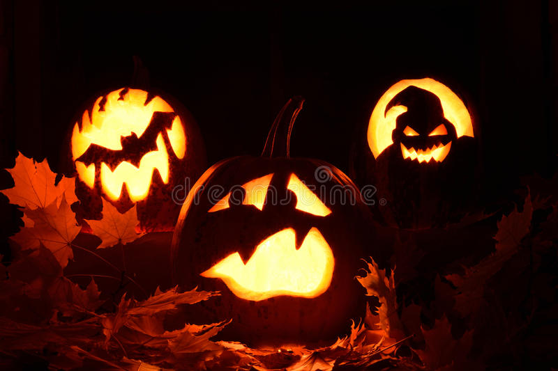 Frightened pumpkin halloween. Photo pumpkins on a table with candles on the background of the window and the moon royalty free stock photos