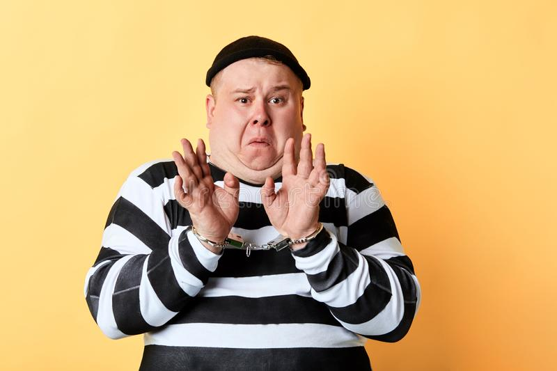 Frightened scared man in stiped clothes standing with raised hands. Being afraid of police, looking at the camera. isolated yellow background stock photos