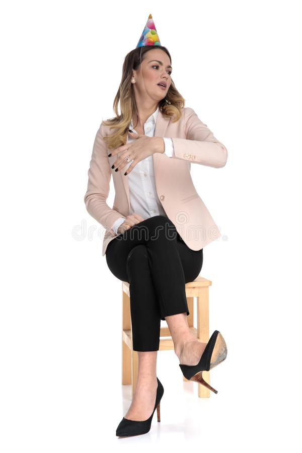 Frightened smart casual woman with birthday hat looks to side. While sitting on wooden chair on white background royalty free stock photography