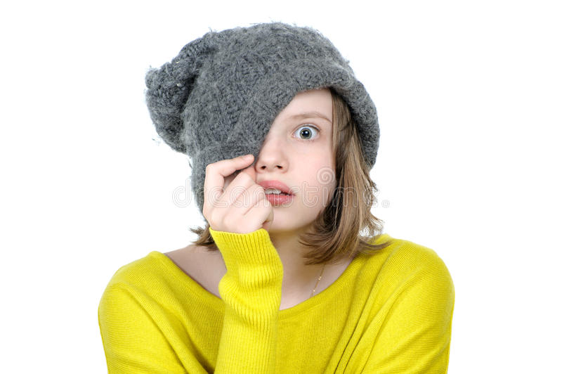 Frightened teen girl covers her face with a cap. royalty free stock images