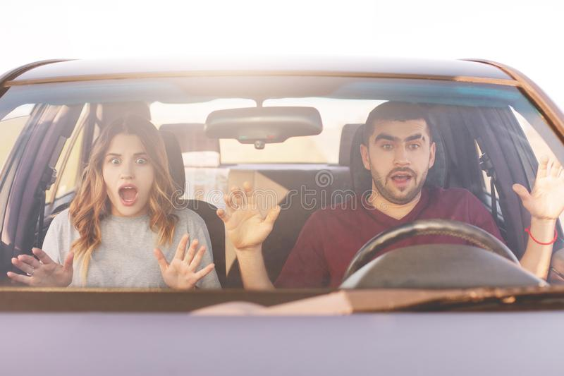 Frightened terrified couple in car can`t control speed, drive fast, afraid of being safe, scream with shock as have accident, bein royalty free stock photo