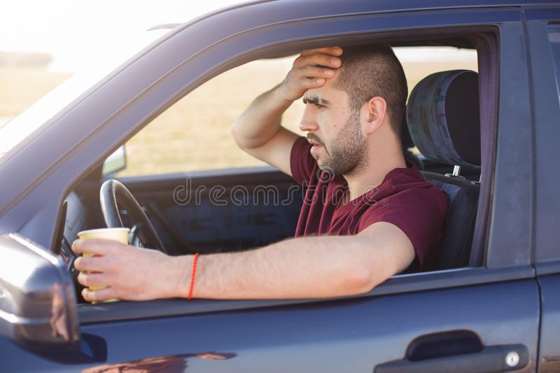 Frightened terrified dark haired unshaved man, stops his car on side of road, drinks tea, sees with shock through windshield at stock image