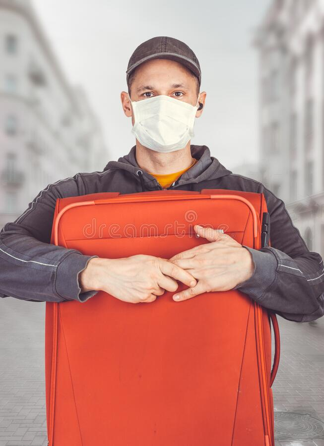 Frightened tourist man in a medical mask presses with red suitcase, the concept cant leave the country, flights canceled. Frightened tourist man in a medical royalty free stock photo