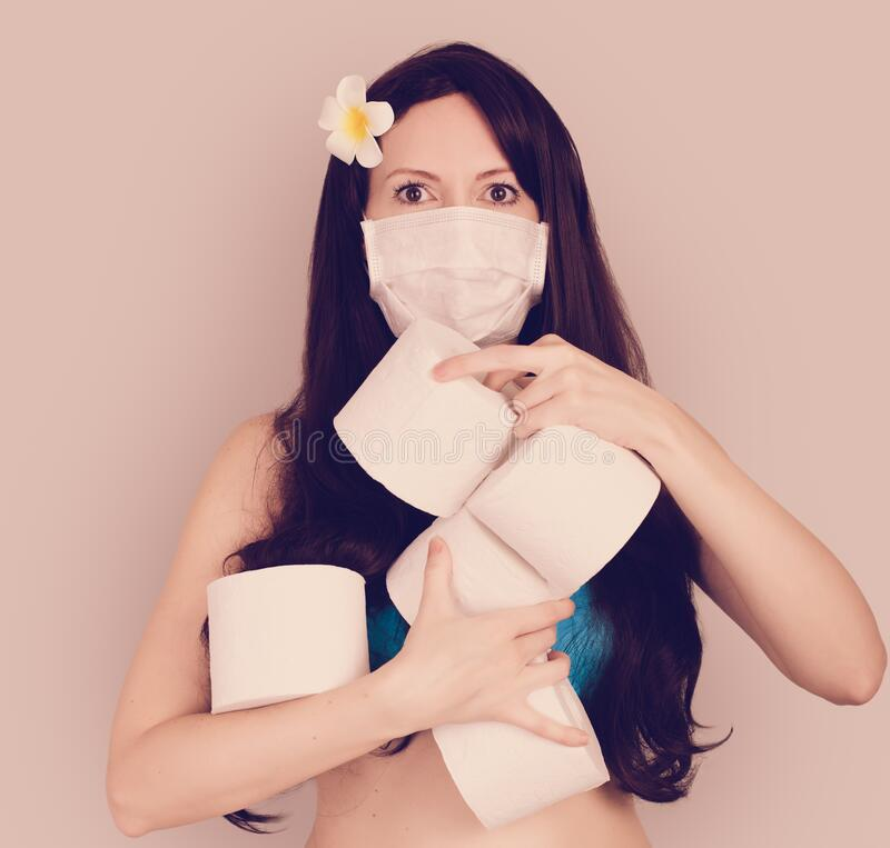 Frightened tourist woman in a medical mask presses with red suitcase, flights canceled. Frightened tourist woman in a medical mask holding toilet paper rolls royalty free stock photos