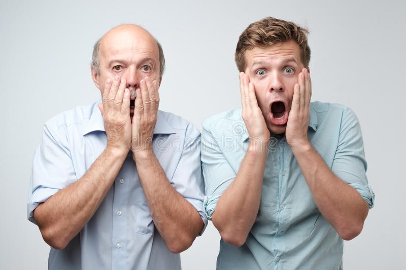 Frightened two men have scared expressions, look nervously, isolated over white background. stock photo