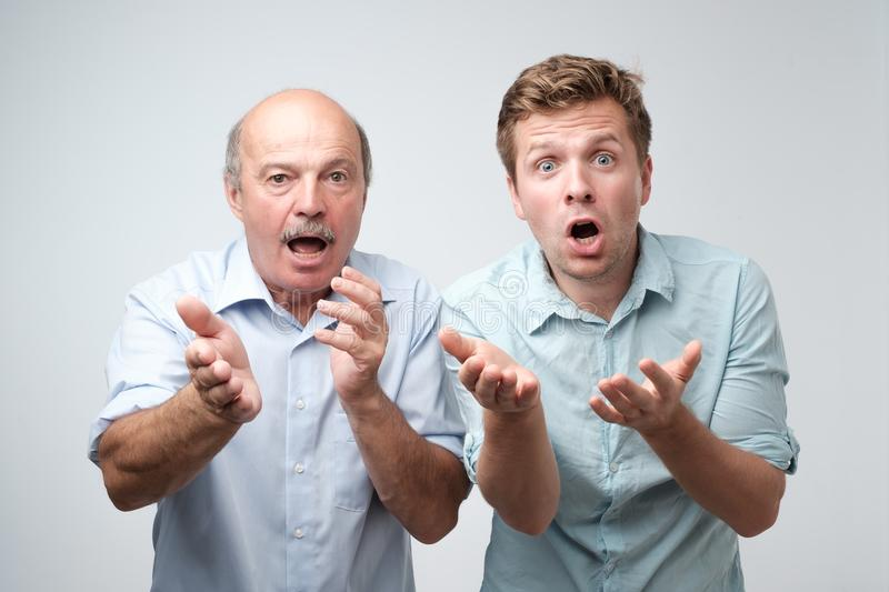 Frightened two men have scared expressions, look nervously, isolated over white background. royalty free stock image