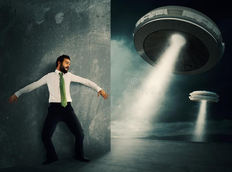 Frightened by UFO. Man hides frightened by UFO space shuttle stock photo