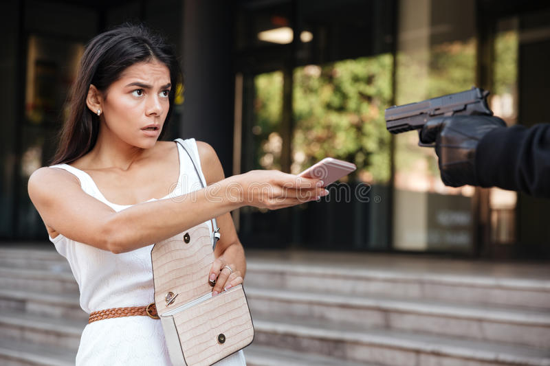 Frightened woman giving mobile phone to robber threatening with gun royalty free stock images