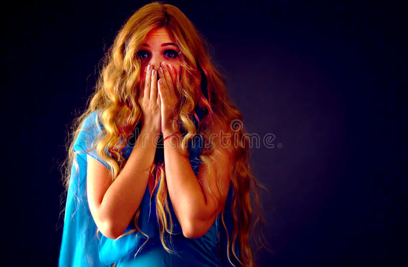 Frightened woman screaming with fear indoor at halloween night. stock photos