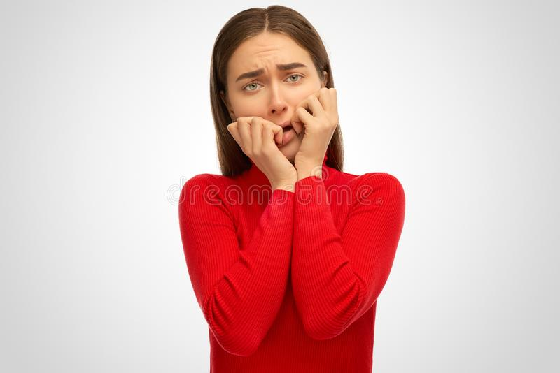 A frightened young girl frowns and covers her face with her hands. royalty free stock photo