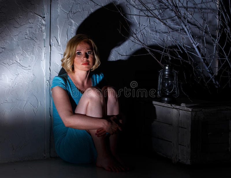 Frightened young woman with extinct lamp sitting in dark place stock photography